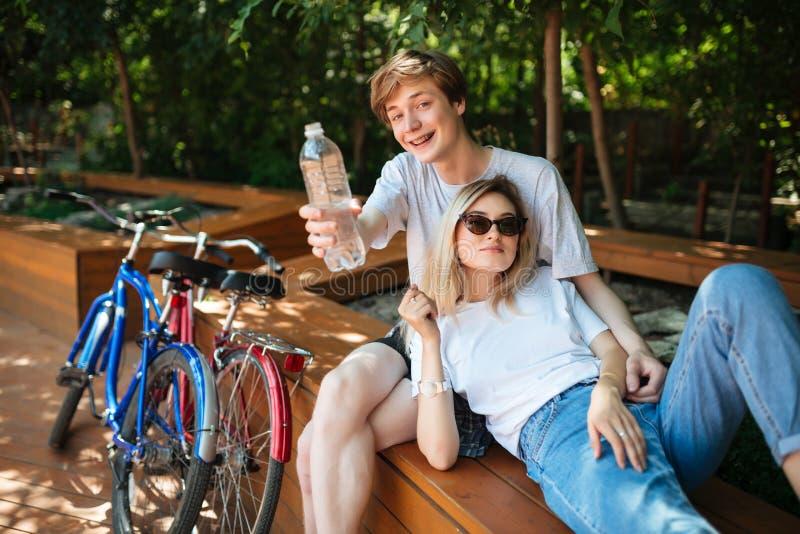 Couples passant le temps sur le banc en bois en parc avec deux bicyclettes près Jeune homme s'asseyant sur le banc et regardant h photographie stock libre de droits