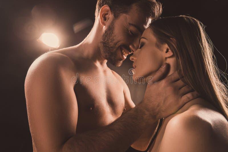 couples passionnés étreignant et souriant, sur le brun images stock