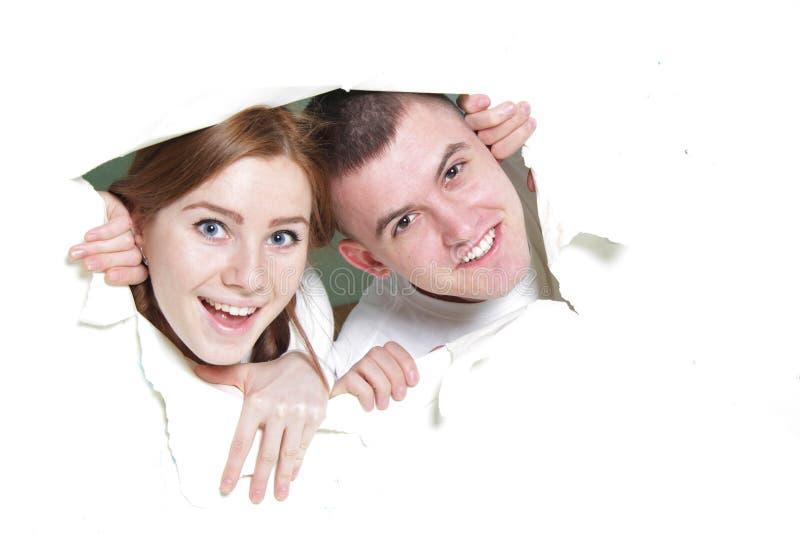 Couples piaulant par le trou en papier photographie stock