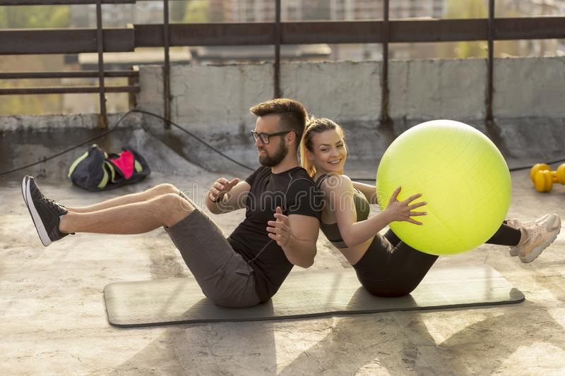 Couples pilates ball workout. Couple sitting back to back on a yoga mat on a building rooftop terrace, exercising by passing the pilates ball to each other royalty free stock photos