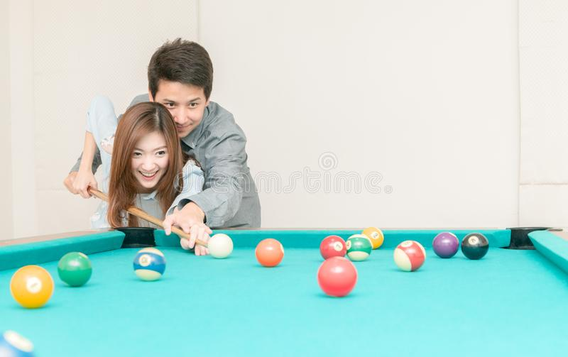 Couples are playing billiards in home stock images