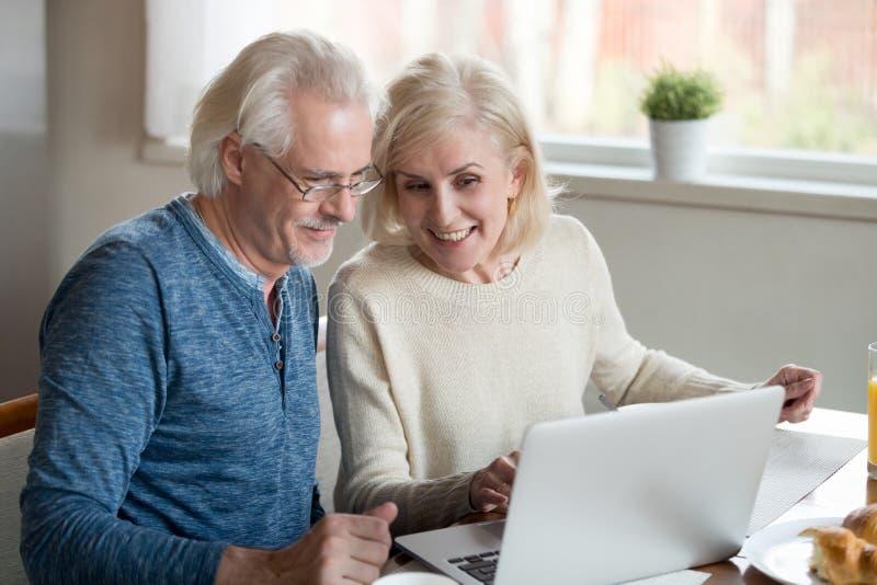 Couples plus anciens heureux de famille parlant utilisant l'ordinateur portable prenant le petit déjeuner image stock
