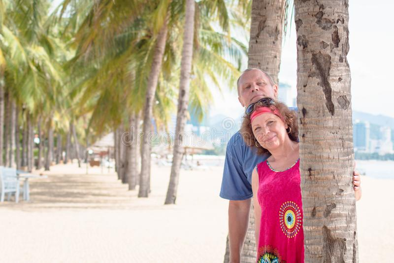Couples pluss âgé à la station de vacances, près de la paume Un homme plus âgé et une femme images libres de droits