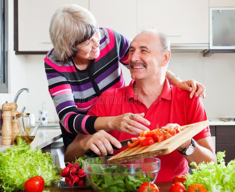 Couples pluss âgé affectueux heureux dans la cuisine image libre de droits