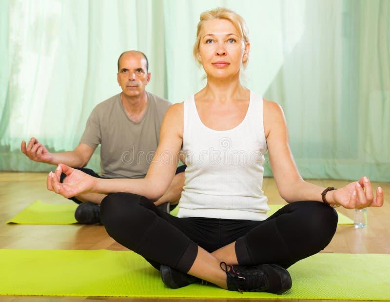 Couples pluss âgé ayant le yoga à la maison image libre de droits