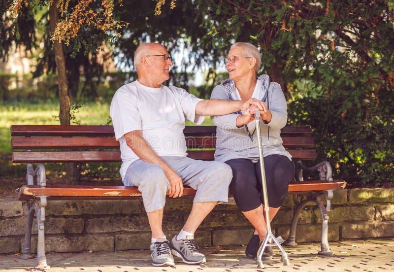 Couples pluss âgé en parc souriant tout en se sentant heureux ensemble image libre de droits