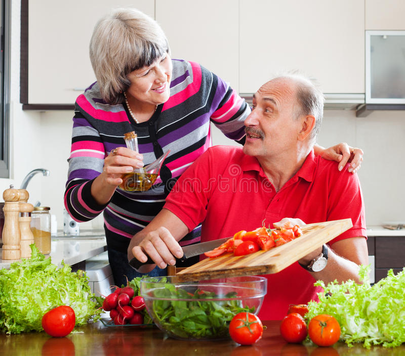 Couples pluss âgé faisant cuire avec des tomates photos libres de droits