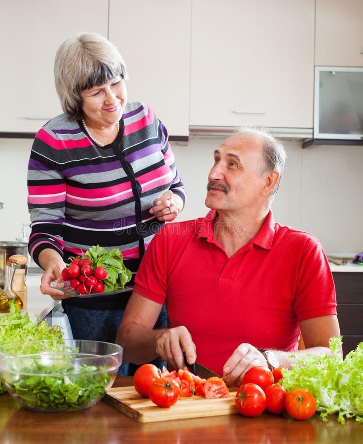 Couples pluss âgé faisant cuire avec les légumes frais image stock