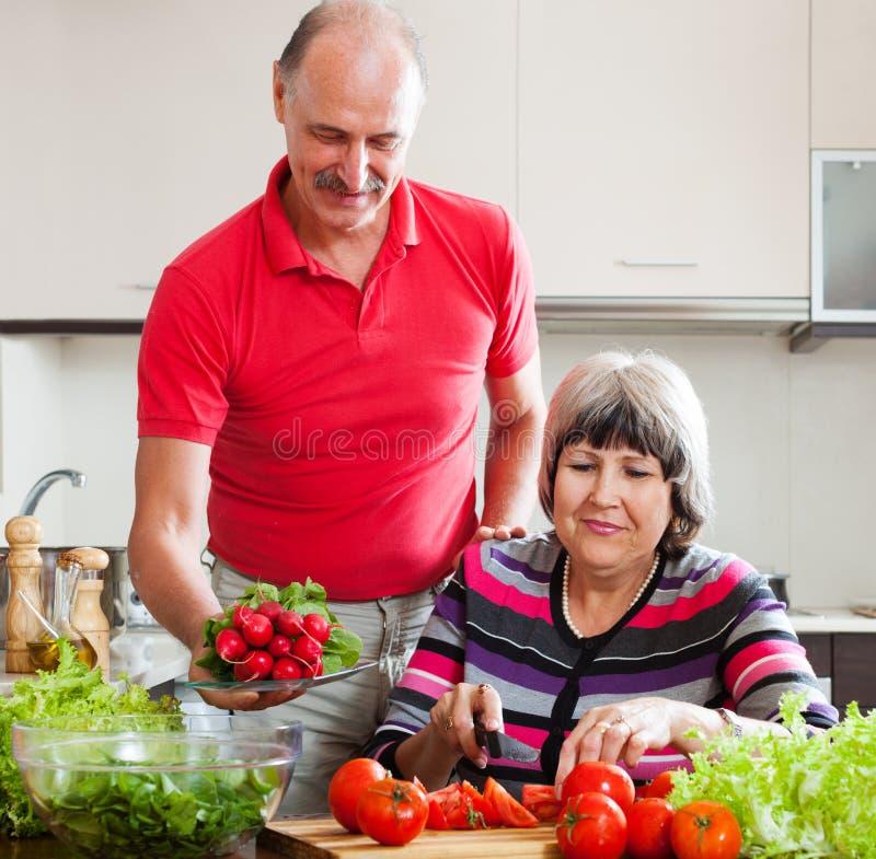 Couples pluss âgé faisant cuire le déjeuner de légumes photographie stock