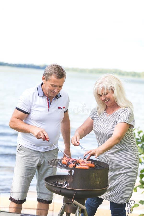 Couples pluss âgé grillant tout entier par le lac photo stock