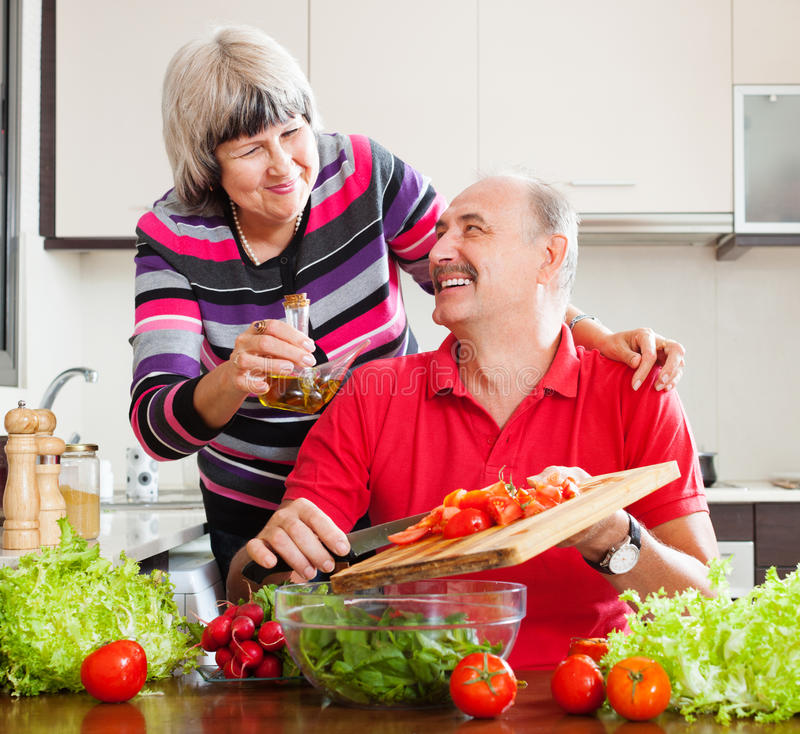 Couples pluss âgé heureux faisant cuire avec des tomates photos stock