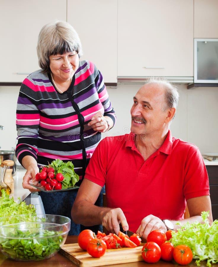 Couples pluss âgé heureux faisant cuire des légumes photographie stock