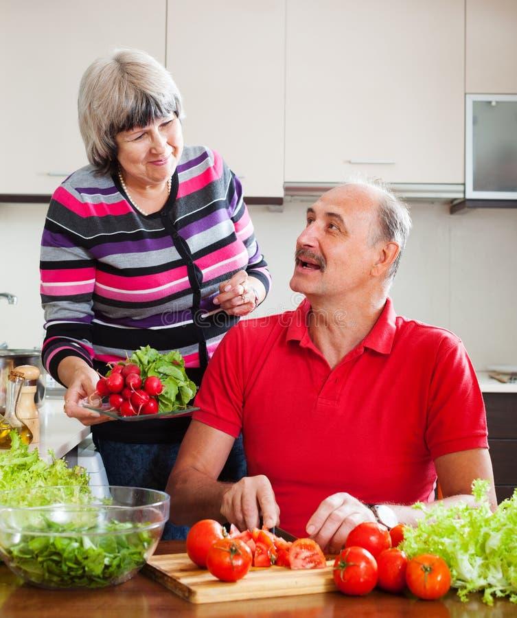 Couples pluss âgé heureux faisant cuire le déjeuner dans la cuisine photo stock