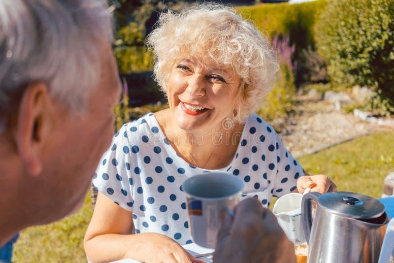 Couples pluss âgé heureux mangeant le petit déjeuner dans leur jardin dehors images libres de droits