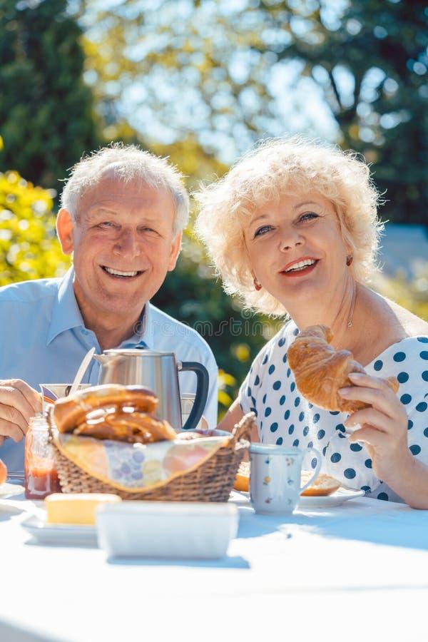 Couples pluss âgé heureux mangeant le petit déjeuner dans leur jardin dehors photos libres de droits