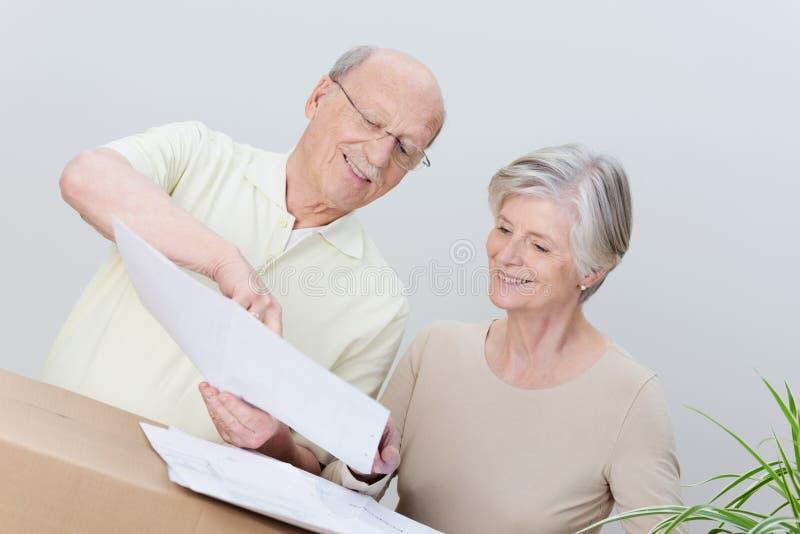 Couples pluss âgé lisant un plan comme ils déplacent la maison photos libres de droits