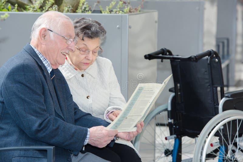 Couples pluss âgé se reposant dehors avec le livre photographie stock