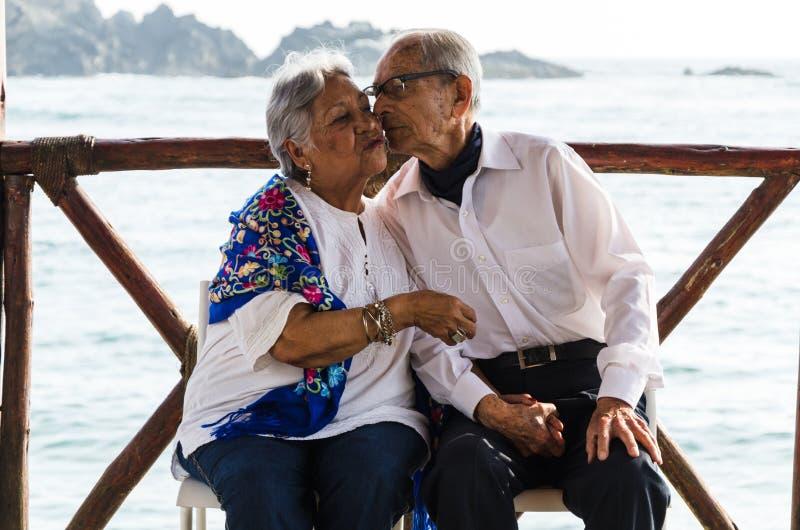 Couples pluss âgé se reposant sur des baisers de chaises photographie stock