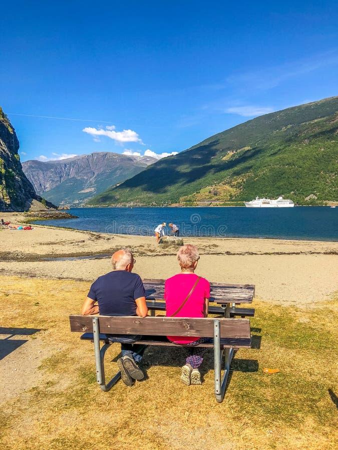 Couples pluss âgé se reposant sur le banc et appréciant la vue sur un fjord image libre de droits