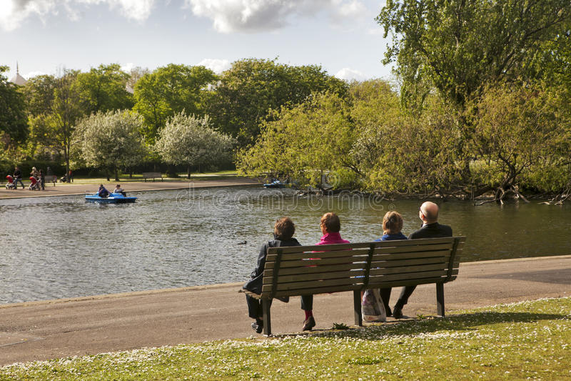 Couples pluss âgé se reposant sur un banc sur un lac image stock