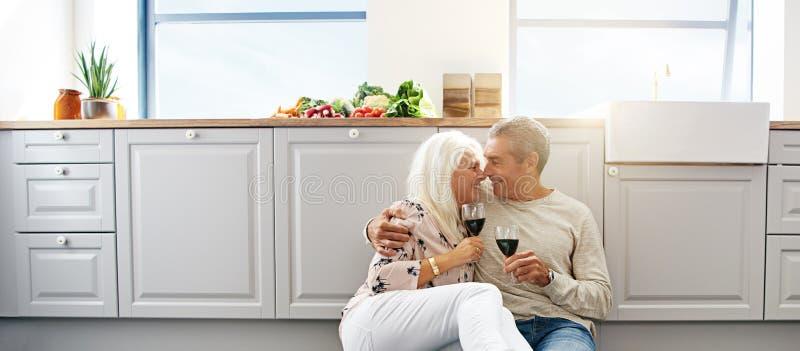Couples pluss âgé sur un plancher de cuisine photos stock