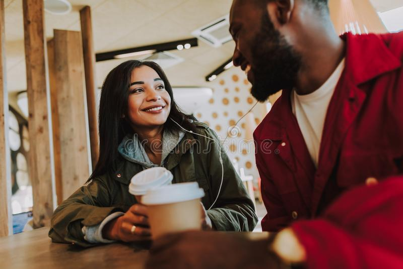 Couples positifs écoutant la musique tout en étant dans le café photos libres de droits
