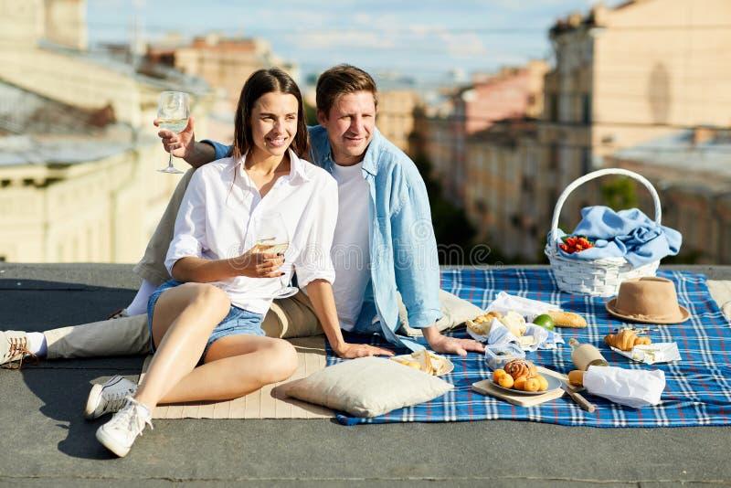 Couples positifs appréciant le pique-nique romantique sur le toit photographie stock libre de droits