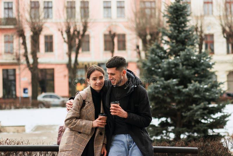 Couples positifs se reposant après promenade, coffe à emporter de boissons photos libres de droits