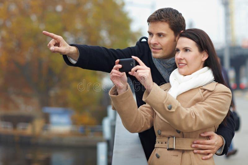 Couples prenant des photos avec le mobile photo stock
