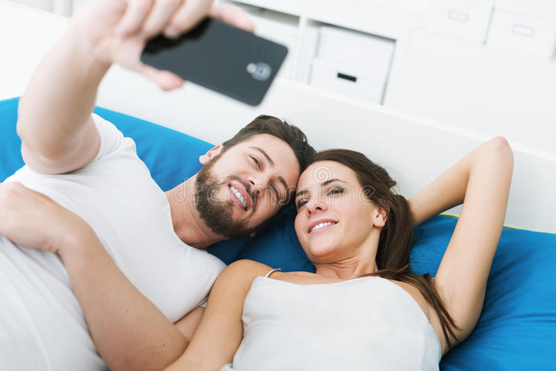 Couples prenant des selfies dans le lit images libres de droits
