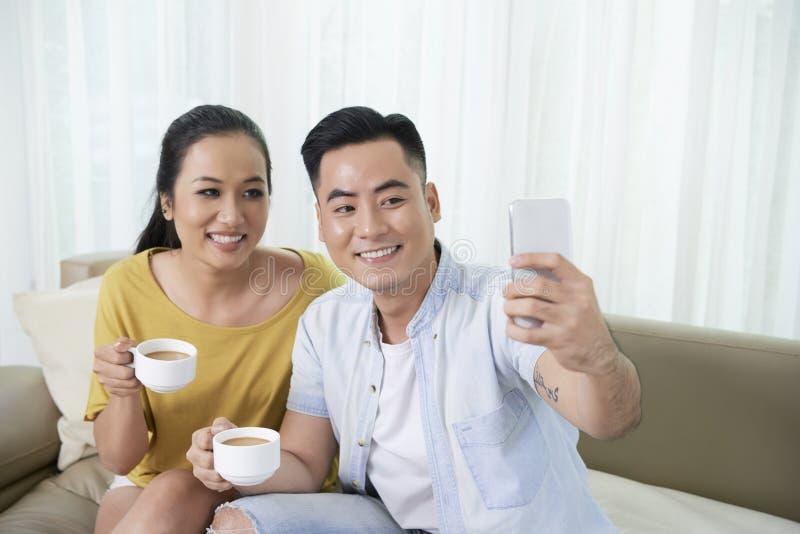 Couples prenant le selfie à la maison images libres de droits