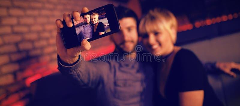 Couples prenant le selfie au téléphone portable dans la barre images libres de droits
