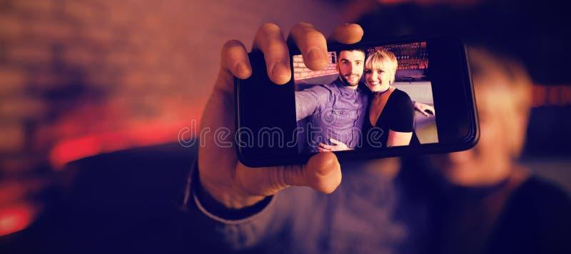 Couples prenant le selfie au téléphone portable dans la barre photographie stock libre de droits