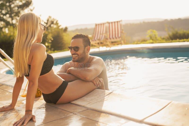 Couples prenant un bain de soleil à une piscine photos libres de droits