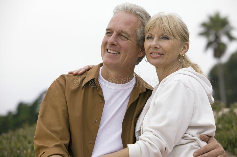 Couples réfléchis s'embrassant sur la plage image libre de droits