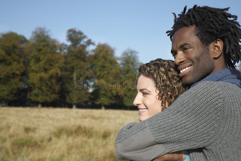 Couples réfléchis semblant partis tout en embrassant dans le domaine photographie stock libre de droits