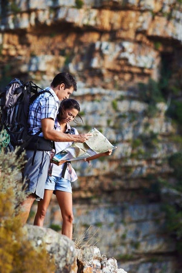 Couples recherchant leur position sur la carte photos stock