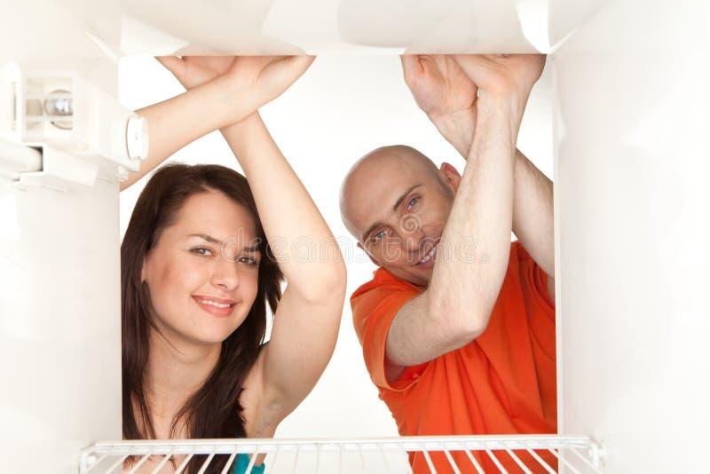 Couples regardant dans le réfrigérateur vide photographie stock