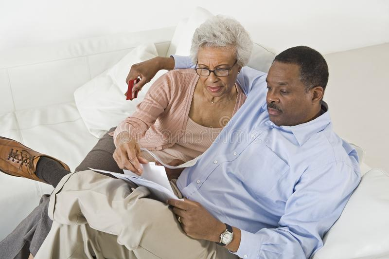 Couples regardant des factures inquiétées avec les finances à la maison photo stock