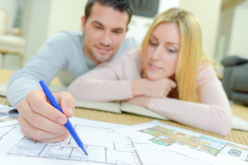 Couples regardant des plans de maison image stock