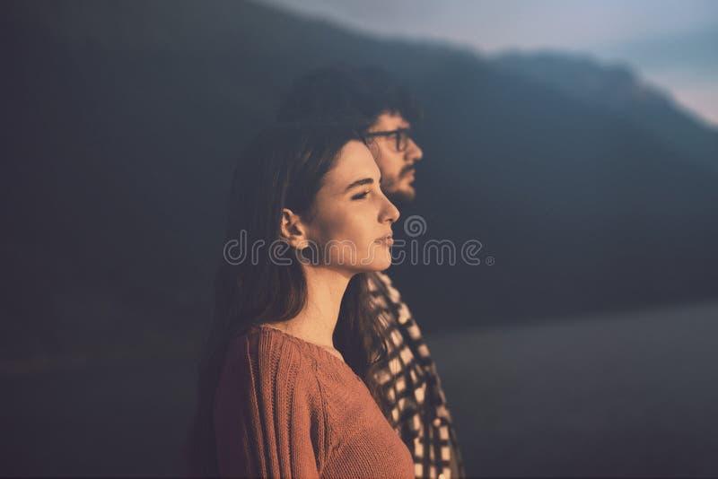 Couples regardant fixement le coucher du soleil dehors photographie stock libre de droits