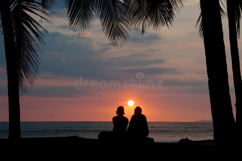 Couples regardant fixement le coucher du soleil tropical sur la plage images stock