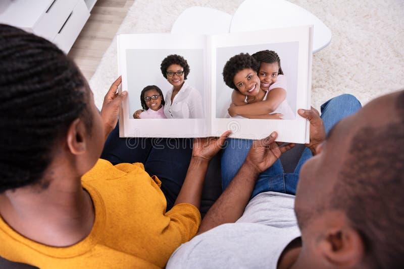 Couples regardant l'album photos de m?re et de fille image libre de droits