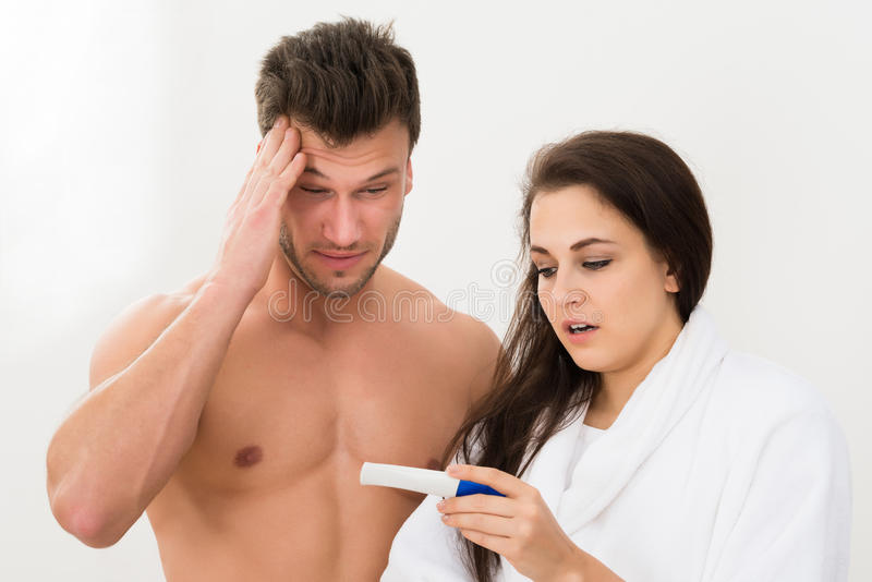 Couples regardant l'essai de grossesse photo stock