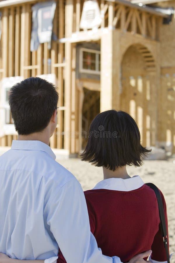 Couples regardant la structure non finie de logement photos stock