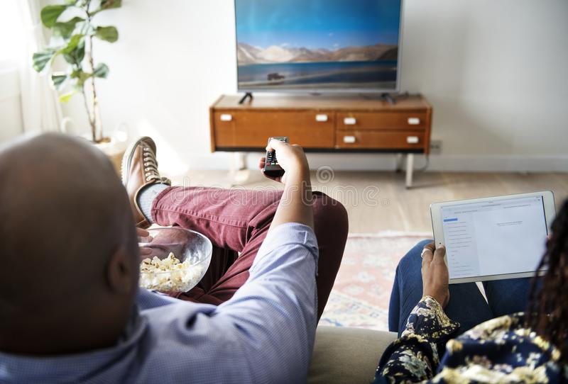 Couples regardant la TV à la maison ensemble photo stock