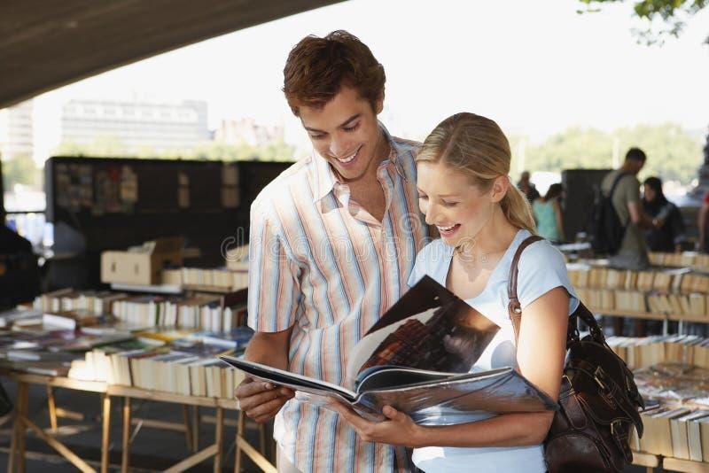 Couples regardant le livre sur le marché de livre images stock