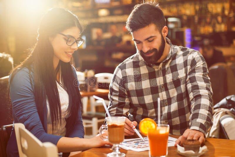 Couples regardant les croquis de mise au point en café photos stock