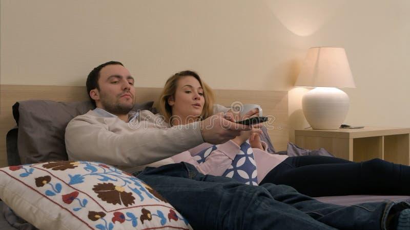 Couples renversants observant un film à la maison image stock