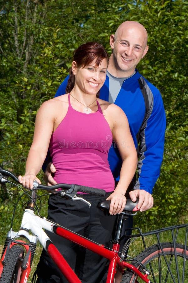 Couples restant à côté du vélo - verticale photo stock